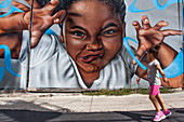 YOUNG AFRO-AMERICAN GIRL PASSING IN FRONT OF A WALL COVERED WITH A MURAL IN THE NEIGHBORHOOD OF BUSHWICK, BROOKLYN, NEW YORK CITY, NEW YORK, UNITED STATES, USA