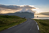 CAR FOLLOWING A WINDING ROAD AT SUNSET, CLIFFS AND OCEAN IN THE BACKGROUND, EIDI, EYSTUROY, FAROE ISLANDS, DENMARK