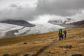 MONGOLIAN RIDER LEADING HIS CUSTOMER IN THE ALTAI MOUNTAINS, THE POTANINE AND ALEXANDER III GLACIERS IN THE BACKGROUND, BAYAN-OLGII PROVINCE, MONGOLIA