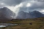 Kasachischer Reiter unter den Lichtstrahlen bei wolkigem Wetter, rötliche Hügel mit schneebedeckten Gipfeln in der Fern, Tavan Bogd Massiv, Altai, Provinz Bayan-Olgii, Mongolei