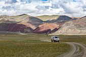 JEEP ON A TRAIL AT THE FOOT OF THE PARTIALLY LIT RED MOUNTAINS, TAVAN BOGD MASSIF, ALTAI, BAYAN-OLGII PROVINCE, MONGOLIA