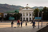 CHILDREN PLAYING SOCCER ON THE MAIN SQUARE IN FRONT OF AN OFFICIAL BUILDING IN THE CITY OF ULGII AND THE SURROUNDING MOUNTAINS, BAYAN-OLGII PROVINCE, MONGOLIA