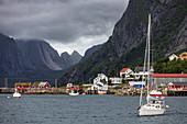 Segelboot und Traditionelle rote Holzhäuser, das Dorf Reine, Vestfjord, Lofoten, Norwegen