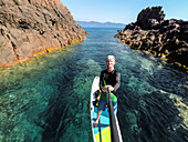 Stand-up paddlers in the Scandola Nature Reserve, Galeria, Calvi, Corsica, France