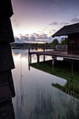 View of fishing huts in Lake Starnberg at sunset, Starnberg; Bavaria; Germany; Europe