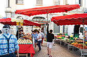 Young man carries parasol through the market stalls in front of the market hall, Les Halles, Redon, Ille-et-Vilaine department, Brittany, France, Europe