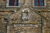 Portal of the Ecole St. Michel from 1891 with a small artistic figure of a boy with twin / slingshot, La Roche-Bernard, Vilaine, Morbihan department, Brittany, France, Europe
