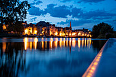 Illuminated house facades by Redon are reflected in the water of the Vilaine river at dusk, Redon, Ille-et-Vilaine department, Brittany, France, Europe