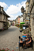 Medieval alley on Place du Puits with people in cafe, Rochefort en Terre, Morbihan department, Brittany, France, Europe