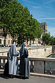 Two nuns eat ice cream and look from Pont Saint-Michel to Notre-Dame Cathedral, Paris, France, Europe