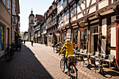 A cyclist in a yellow jacket leads towards the Sankt-Michael church through a half-timbered street with shops, Short Street, G? Ttingen, Lower Saxony, Germany, Europe