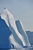 Disco bay; West Greenland; Iceberg in the Kangia Icefjord near Ilulissat; impressive ice formation; towering steep wall with scale-like surface; Ice surfaces shine in the sun; smooth transitions; blue sky and sunshine