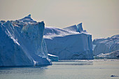 Disco bay; West Greenland; Icebergs at Ilulissat; diverse ice formations with steep walls, cracks, peaks and scaly surfaces; calm water surface; nice weather; dazzling sunlight