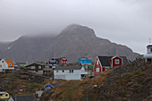 Sisimiut in West Greenland; second largest city in Greenland; Cityscape; colorful wooden houses in rocky, hilly terrain; above-ground water pipes supply all buildings in the village; Mountain backdrop with rocky cliffs in the background; low-hanging rain clouds cover the mountain tops of Nasaasaaq;