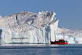 Disco Bay in West Greenland; Icebergs in the Kangia Icefjord near Ilulissat; red tour boat with visitors approaches an iceberg; Steep walls and demolition areas; Sun and cloudless sky;