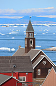 Zionskirche in Ilulissat; Disco Bay in West Greenland; Church covered with brown painted wood; white window frames and roof edges; in the foreground sections of wooden houses; in bright red and light brown; behind the church is the Disko Bay with icebergs and ice floes; mountain ranges in the background