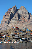 "Uummannaq Island in West Greenland; homonymous place below the heart-shaped mountain; ""Uummannaq"" is the name of the seal heart; View of the with harbor and colorful apartment buildings; Houses stand on rocky, steep terrain;"
