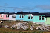 colorful, wood-clad rainbow-colored houses; Qeqertarsuaq on Disko Island in West Greenland; in the foreground grassy hills and partly rocky terrain;