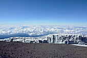 View from the summit of Kilimanjaro; Remains of the glacier field; Lava debris; infinite sea of clouds;