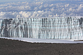 View from the summit of Kilimanjaro to the glacier wall; Lava oil, partly covered with snow; behind it sea of clouds;