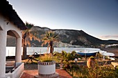 Fisherman's house with palm trees at Porto Levante on the island of Vulkano, Aeolian Islands, southern Italy