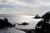 Sea backlit, silhouette, Isola Bella under Taormina, east coast, Sicily, Italy