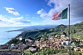 Italian flag and view and sea and coast, Santuario Madonna della Rocca, Taormina, east coast, Sicily, Italy