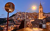 Evening, church, houses on the hill, lights on the Duomo, upper town of Modica, southern Sicily, Italy