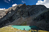 Man at mountain lake Vorderee in front of rocky backdrop in Gradental, Hohe Tauern National Park, Austria