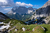 Hikers in the Seebensee panorama in spring with Zugspitze, clouds in the sky, Ehrwald Austria