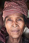 Kambodscha - 18. Januar 2011: Eine lächelnde kambodschanische Frau mit rotem kariertem Schal auf dem Kopf