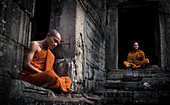 Siem Reap, Cambodia - January 19, 2011: Two monks in their orange robe are sitting and meditating in the Angkor Wat complex.