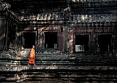 Siem Reap, Cambodia - January 19, 2011: A monk in his orange robe at the Angkor Complex.