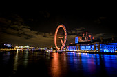 The impressive London Eye also known as the Millennium Wheel by night in London, United Kingdom. This ferris wheel is located on the South Bank of the River Thames and is one of the main tourist attraction.
