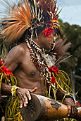 Papua New Guinea - November 8, 2010:  A man with tribal face painting and wearing special clothing is playing a Kundu Drum on a festival.