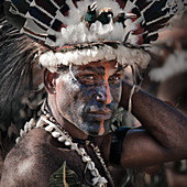 Alotau, Papua New Guinea - November 6, 2010: A man with tribal face painting is wearing hat with feathers at the Kenu and Kundu Canoe Festival.