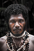 Papua New Guinea - November 8, 2010: A man with tribal face painting and shell necklace.