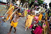 Singapore - January 17, 2014: A big group of Tamil people are celebrating the Thaipusam Hindu festival on the street. Piercings on the body demonstrate their faith during the festival.