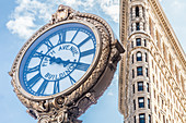 Golden clock in front of the Flatiron Building, New York City, USA