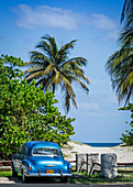 Vintage car on the beach with palm trees, Varadero, Cuba