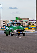 Vintage car drives along the Malecon, Havana, Cuba