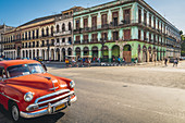 Classic red car is parked near the Capitol, Havana, Cuba