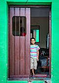 Cuban boy stands at the door, Camagüey, Cuba