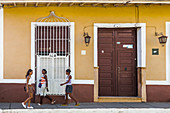 Three women walk in Trinidad, Cuba