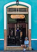Cubans sit in front of a bar in Trinidad, Cuba