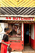 Kenyan woman with her child in front of a butcher shop in the slum, Eastleigh, Nairobi, Kenya