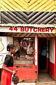 kenianerin mit Ihrem Kind vor einer Metzgerei im Slum, Eastleigh, Nairobi, Kenia