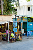 Market women in front of fruit and vegetable stall and fish shop, Watamu, Malindi, Kenya