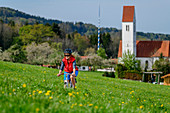 Woman cycling in front of Kematen church, tree-to-tree bike path, Upper Bavaria, Bavaria, Germany