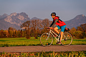 Woman cycling with Heuberg in the background, tree-to-tree cycle path, Bad Feilnbach, Upper Bavaria, Bavaria, Germany